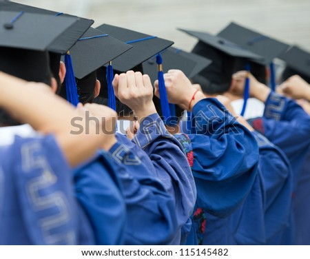 back of graduates put hands up during commencement. - stock photo