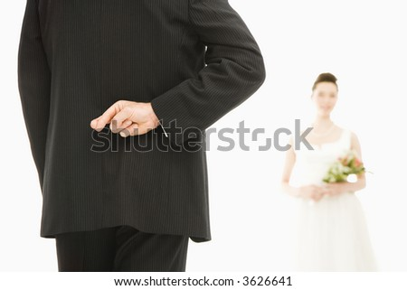 Back of groom with his fingers crossed and Asian bride in background.