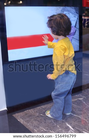 Back of little boy in jeans touching big advertising display at mall.