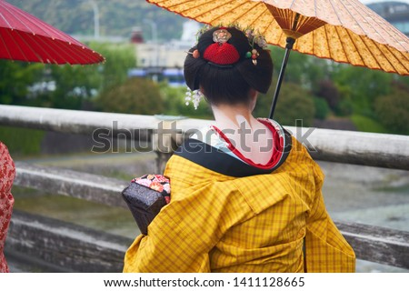 Back of Maiko, Apprentice Geisha who Entertain Through Traditional Art of Dancing, Singing in Yellow Traditional Costume Hold Paper Umbrella Walking on Bridge across Kamogawa River in Kyoto Japan #1411128665