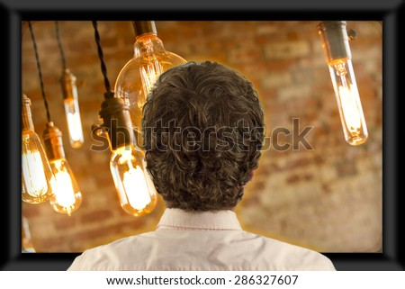 Back of man\'s head as he\'s watching flat screen television