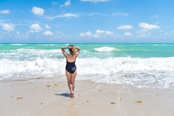 Back of one young female woman in one piece swimsuit standing or walking on sea ocean shore coast in Miami, Florida beach with waves by horizon
