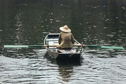 Back of rowing boat man wearing green shirt and conical hat sitting in a boat with paddles over the river in background at Trang An Grottoes in Ninh Binh, Vietnam.