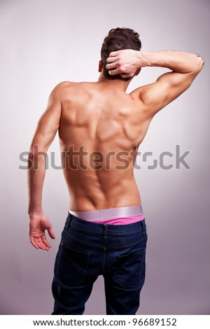 Back of sexy muscular man on gray background. back picture of a shirtless man in a fashion pose