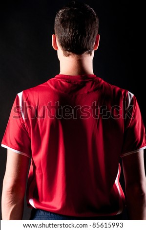 back of soccer player on black background