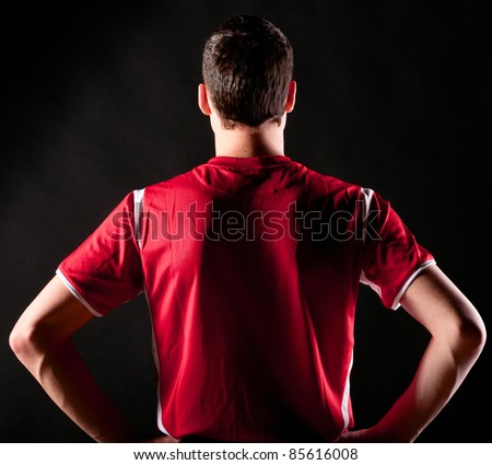 back of soccer player on black background