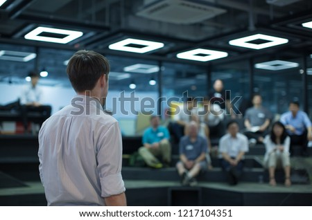 Back of Speaker Giving Lecture at Tech Business Seminar. Audience at Conference Hall. Business Entrepreneurship Event. Young Presenter Gives Presentation Talk During Conference. Technology Workshop