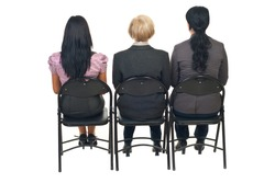 Back of three business women sitting on chairs at  presentation isolated on white background
