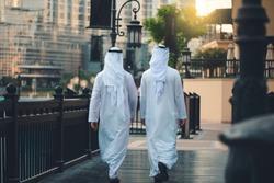back of two Arabic men walking in Dubai downtown
