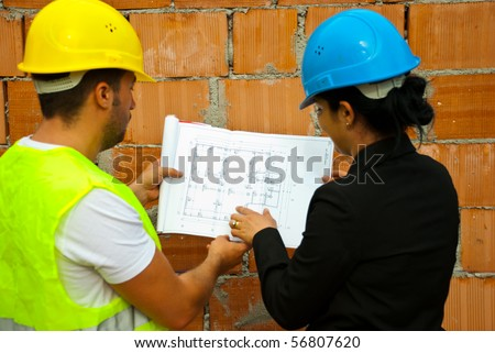 Back of two architects with helmet working in a house under construction and holding blueprints,selective focus on plan