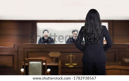 back of woman authorny on courtroom talking to magistrate in court. The law adjustment concept.back of attastor talking to magistrate in court. the law adjustment concept