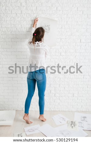 Back of woman hanging her sketch on wall. Female artist evaluate her painting performance, trying it on white brick wall, free space for text