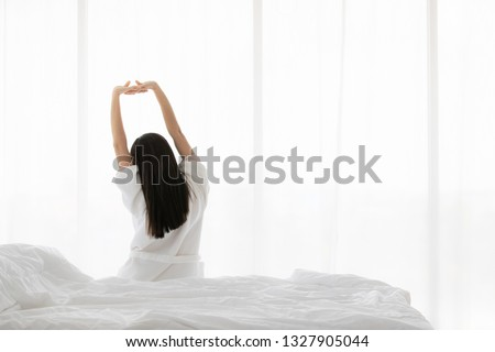 Back of woman on bed in the morning, stretching hands and body. Concept for start new day with happiness. Copyspace on the right.