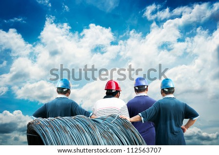 back of workers with blue sky