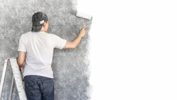 back of young asian man on ladder painting interior cement wall with paint roller for home renovation background