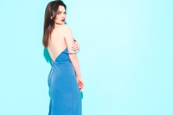 Back of young beautiful brunette woman wearing nice summer dress.Sexy trendy model posing near blue wall in studio.Fashionable female looking at camera. Red lips