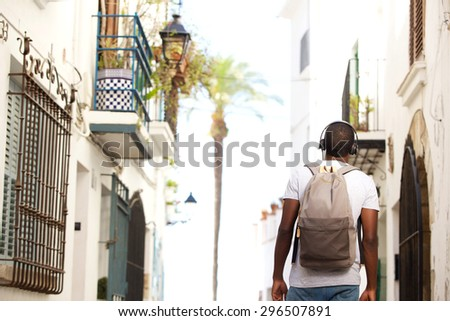 Back of young black man waking in town with bag and headphones