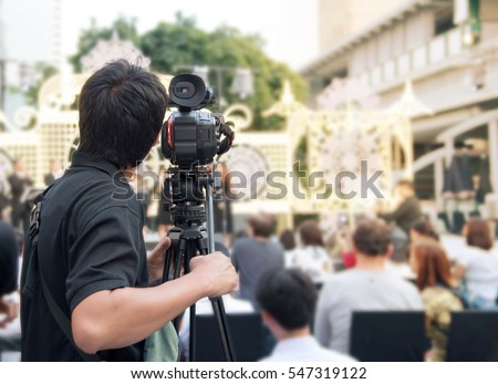 Back of young cameraman using a professional camcorder outdoor  filming music show or mini concert with blur background, Bangkok, Thailand #547319122