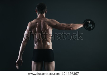 Back of young male bodybuilder doing weight exercise with dumbbells