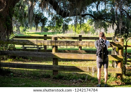 Back of young man, nature photographer standing, taking pictures of landscape in Gainesville, USA Paynes Prairie Preserve State Park in Florida, wooden fence paddock stable