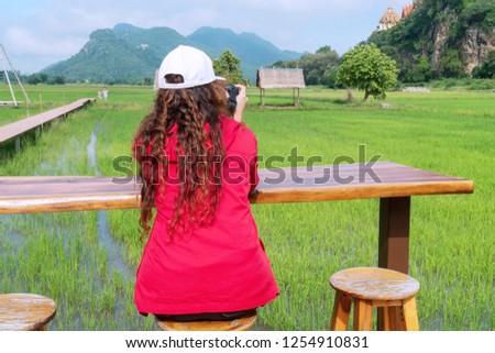 Back of young woman wearing red jacket with white hat use dslr camera taking photo. Traveler photographer take photo landscape cornfield at outdoor coffee shop.
