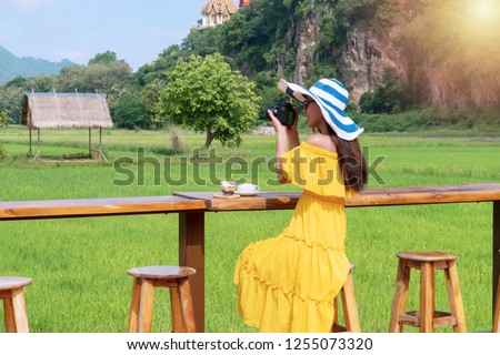Back of young woman wearing yellow dress with hat use dslr camera taking photo. Traveler photographer take photo landscape cornfield while sitting in outdoor coffee shop.