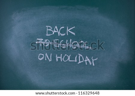 Back on holiday concept. Writing back to school scored out and replaced with text back on holiday, school chalkboard (blackboard).