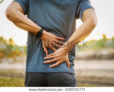 Back pain, close up young man has injury during outdoor exercise #1020731773