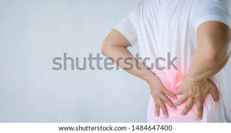 Back pain concept, kidney inflammation, man suffering from backache at home, red inflamed zone, panorama. Wearing a white shirt, gray background