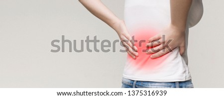 Back pain, kidney inflammation, woman suffering from backache, red inflamed zone, panorama