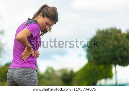 Back pain - woman having painful muscle injury in lower back