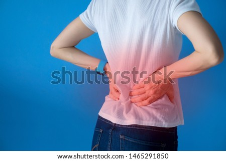 Back pain, woman suffering from backache isolated on blue background, painful area highlighted in red