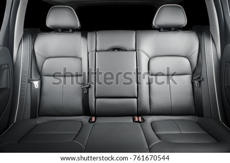 Back passenger seats in modern luxury car, frontal view, black perforated leather