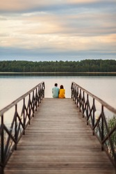 Back perspective view of serene young couple sitting on wooden pier and enjoying beautiful river scenery together in warm summer evening