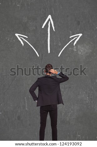 back picture of a confused business man thinking wich way to go