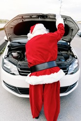 back portrait of Santa Claus with the bonnet car and looking at the engine because his car broke down and he can't deliver the children's gifts in Christmas 2020