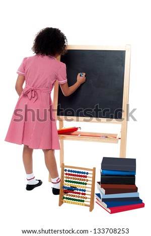 Back pose of a school girl finding solution and solving problems in maths class.