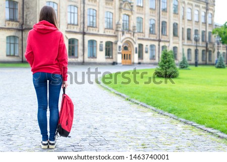 Back rear behind full length bosy size photo of serious confident concentrated hipster holding schoolbag in hand looking at the entrance standing near green lawn Foto stock ©