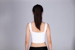 Back rear side view of Asian people present Hair style of black pony tail straight and wrap hair of woman in sport bra fitness dress, studio lighting gray background isolated half body