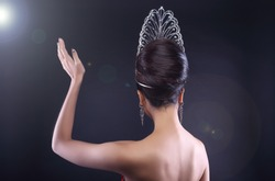 Back rear side view Portrait of Miss Pageant Beauty Contest in Red sequin Evening Gown with Diamond Crown wave hand, Asian Woman fashion make up hair style, studio lighting dark background copy space