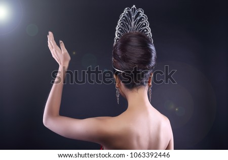 Back rear side view Portrait of Miss Pageant Beauty Contest in Red sequin Evening Gown with Diamond Crown wave hand, Asian Woman fashion make up hair style, studio lighting dark background copy space #1063392446