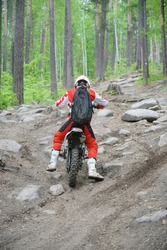 back rear view. Extreme sports on motorcycle. A rider on a enduro bike rides the hill. Dangerous sport and hobby. Racer woman on motocicle in red and white clothes.