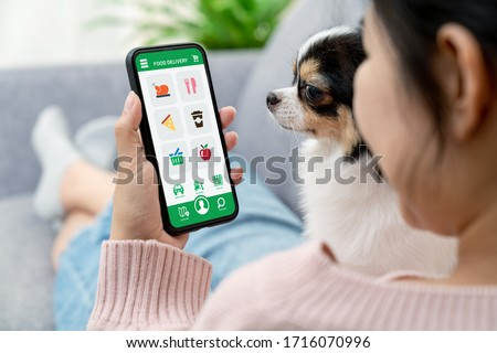 Back rear view of young asian teenage girl in concept next normal life from coronavirus impact sitting at sofa couch with dog hand holding smart phone at home. Food or grocery delivery order service.