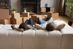 Back rear view tired young family couple lying on comfortable sofa, resting after hard moving day near huge carton boxes. Satisfied new homeowners relaxing on couch in modern renovated living room.