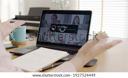Back rear view young asian woman employee work from home using computer notebook videocall meeting conference angry annoy with low poor unreliable internet wifi connection problem issue outage. Stock foto ©