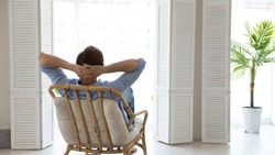 Back rear view young caucasian man relaxing on comfortable chair with folded arms behind hand, looking out of window, contemplating or daydreaming alone in light living room, enjoying peaceful moment.
