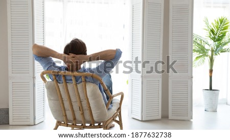 Back rear view young caucasian man relaxing on comfortable chair with folded arms behind hand, looking out of window, contemplating or daydreaming alone in light living room, enjoying peaceful moment. Foto stock ©