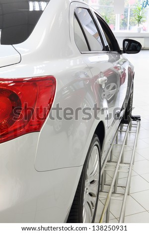 Back red lights of new white shining car standing in office of shop selling cars.
