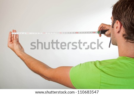 back shot of a caucasian male measuring against a light background
