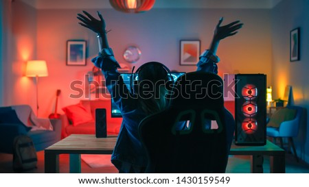 Back Shot of a Gamer Girl Playing and Winning in First-Person Shooter Online Video Game on Her Powerful Personal Computer. Room and PC have Colorful Neon Led Lights. Cozy Evening at Home.